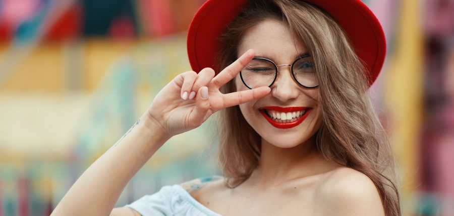 Cheerful girl making funny faces on colorful background. Party's soul winking and showing victory sign while smiling