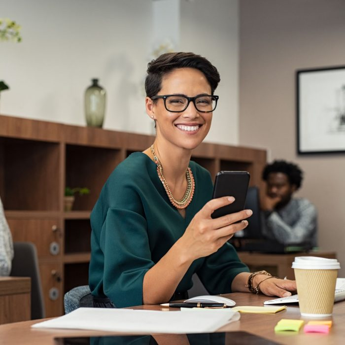 Happy fashionable girl using smartphone while working on desktop computer. Cheerful young business woman sitting in coworking space typing on smart phone and looking at camera. Portrait of  freelancer with eyeglasses working in office.
